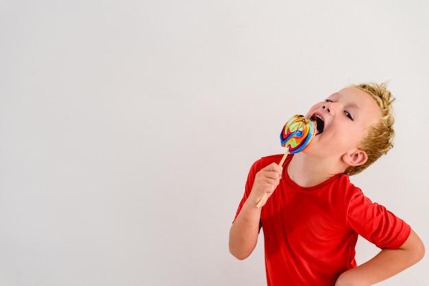 Garçon avec une chemise rouge sur fond blanc, manger une sucette amusante colorée et rire.