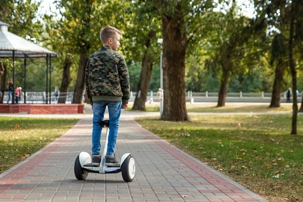 Un garçon chevauchant un hoverboard dans le parc