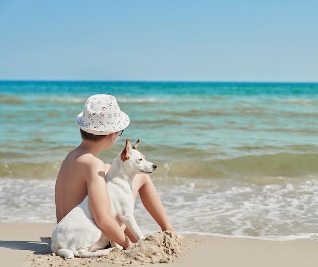 Garçon avec un chien jack russel sur la plage