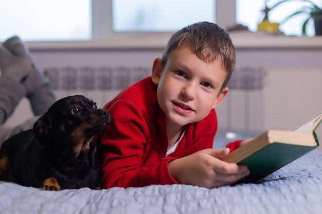 Garçon avec chien lit un livre