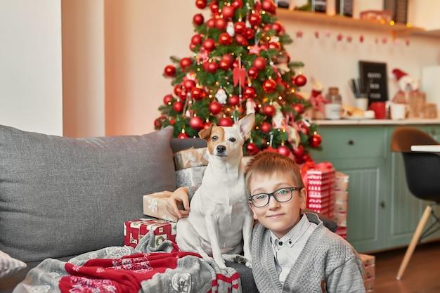 Garçon avec chien près de sapin de noël sur fond de noël