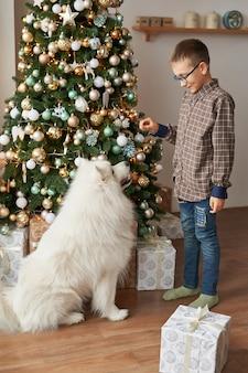 Garçon avec chien près de sapin de noël