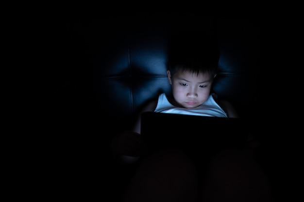 Garçon chinois asiatique jouant au smartphone dans la pièce sombre, jeu et dessin animé accro aux enfants