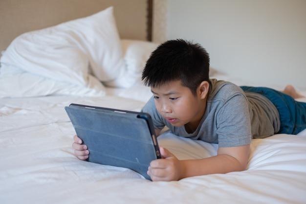 Garçon chinois asiatique jouant au smartphone, enfant utilise un téléphone et joue à un jeu, un jeu accro et un dessin animé