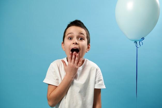 Un garçon choqué couvre sa bouche tout en regardant à l'avant et exprimant sa surprise debout sur une surface bleue avec copie espace