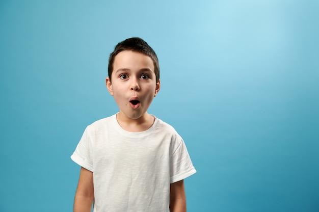 Garçon choqué posant avec la bouche ouverte exprimant la surprise sur la surface bleue avec copie espace