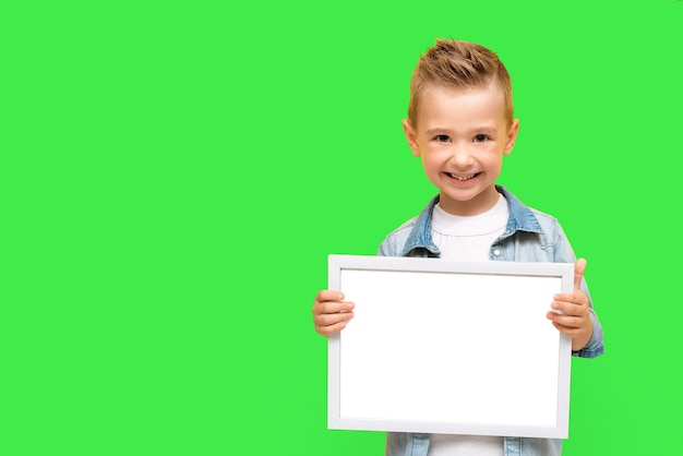 Un garçon de cinq ans sourit et tient un cadre blanc vierge. joyeux enfant d'âge préscolaire isolé sur fond vert avec espace de copie pour le message, l'information, la maquette. kid tenir un grand cadre photo.