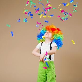 Garçon de clown heureux avec une grande perruque colorée