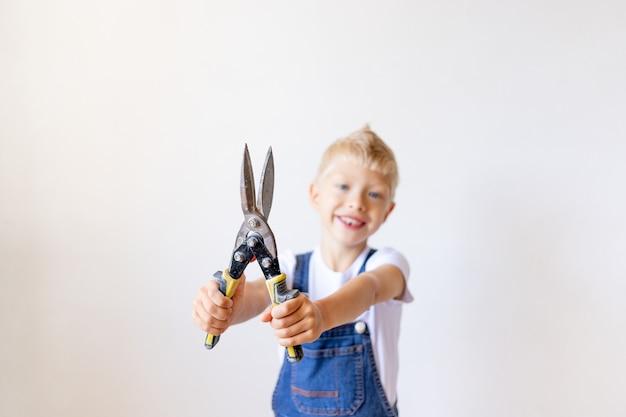 Garçon en combinaison jouant avec l'outil mécanique