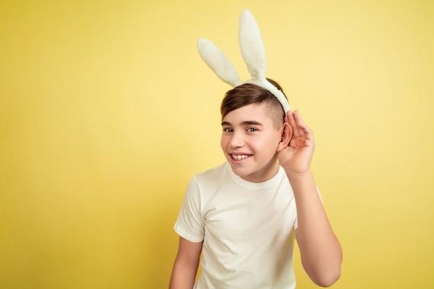 Garçon comme un lapin de pâques sur le mur jaune du studio