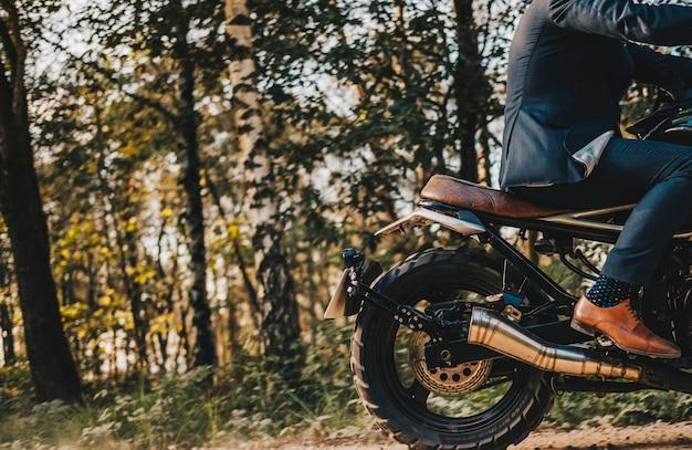 Un garçon conduire une moto sur la route de pierre