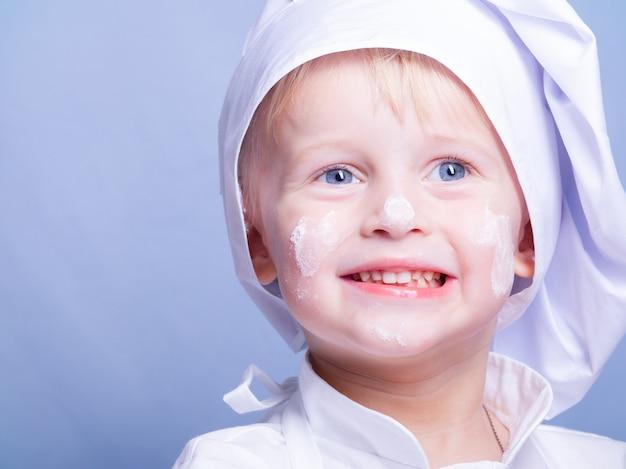 Garçon en costume et une casquette de chef sourit