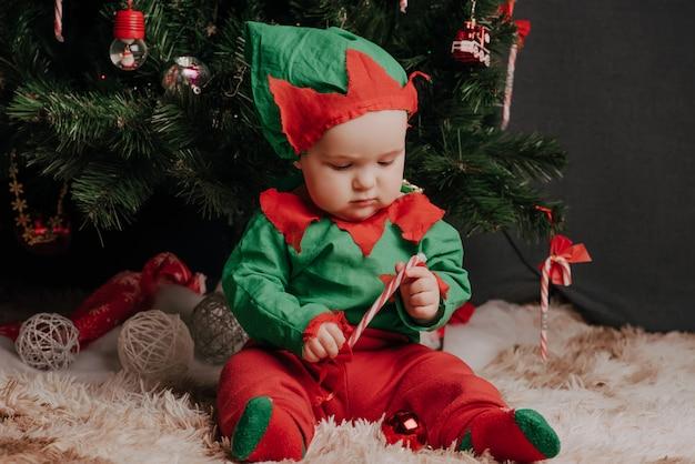 Garçon en costume d'elfe assis sous un arbre de noël avec une sucette