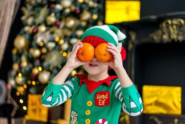 Un garçon en costume d'elfe avec des mandarines à l'arbre de noël attend noël