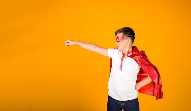 Un garçon en costume de héros et un masque se dresse sur un fond jaune avec une place pour le texte
