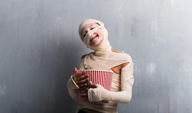 Garçon en costume de momie mangeant des popcorns pour les fêtes d'halloween