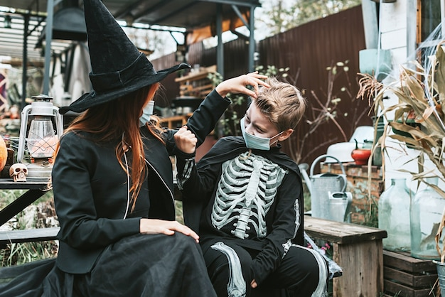 Un garçon en costume de squelette et une fille en costume de sorcière portant un masque protecteur lors d'une fête d'halloween dans une nouvelle réalité en raison de la pandémie de covid