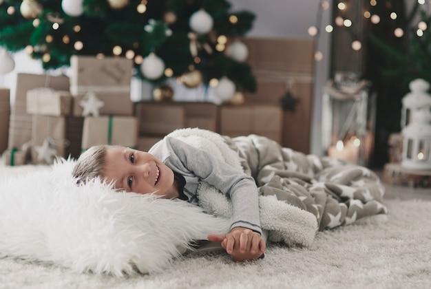 Garçon couché sur un tapis dans le salon