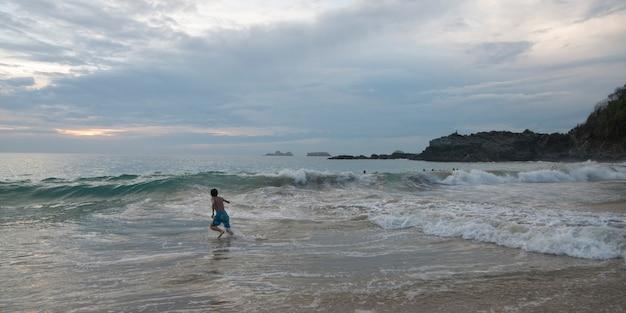 Garçon courant dans les vagues sur la plage, zihuatanejo, guerrero, mexique