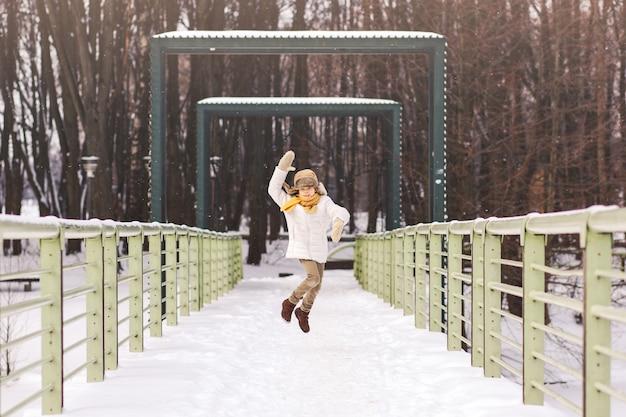Garçon court et s'amuse en hiver dans le parc