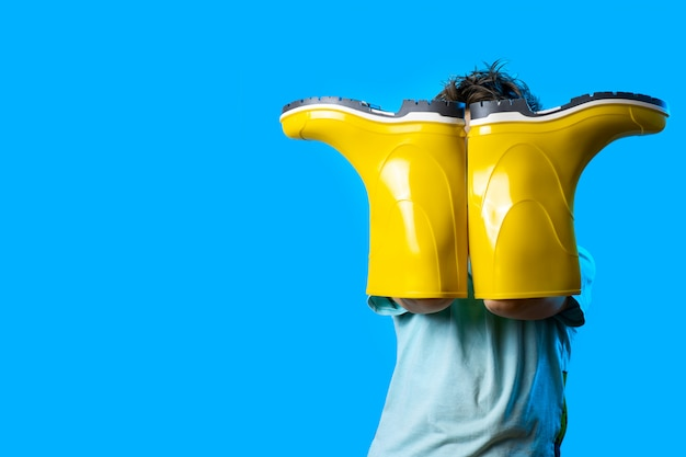 Un garçon a couvert son visage avec des bottes en caoutchouc jaune