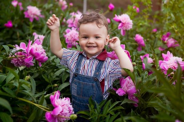Le garçon dans les buissons de pivoines roses, le cri de la victoire.