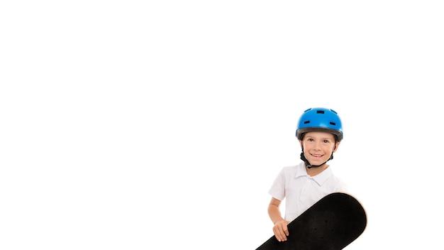 Garçon dans un casque bleu avec une planche à roulettes dans ses mains et un sourire radieux sur son visage, il est heureux