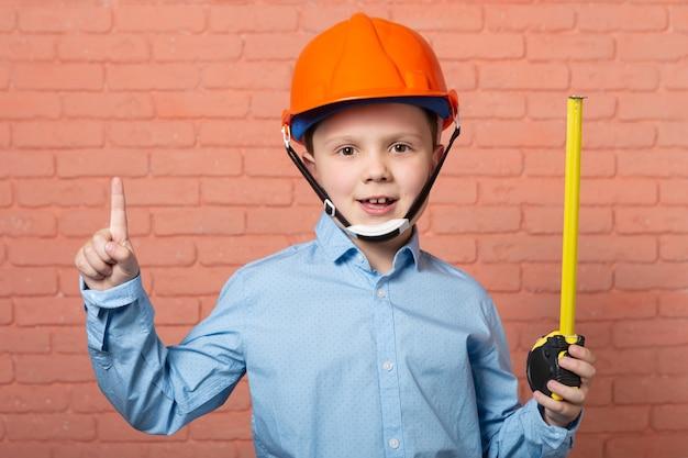 Garçon dans un casque de chantier orange avec un ruban à mesurer à la main sur fond de brique