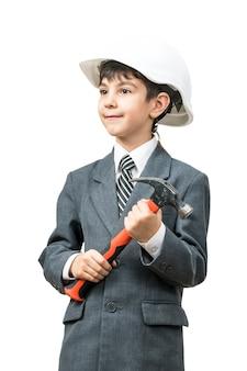 Garçon dans le casque de construction et veste tenant un marteau