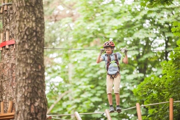 Un garçon dans un casque et un équipement de sécurité dans un parc de cordes d'aventure sur fond de nature