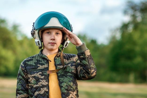 Un garçon dans le casque d'un pilote salue.