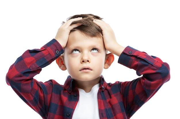 Un garçon dans une chemise à carreaux rouge tient sa tête avec ses mains. isolé sur blanc. fermer.