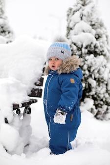 Un garçon dans une combinaison bleue et un chapeau voit la neige pour la première fois et se tient près d'un banc dans le contexte d'un arbre de noël enneigé dans le parc.