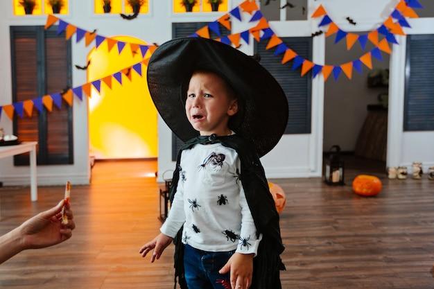 Un garçon dans un costume de carnaval et un chapeau noir va à la fête d'halloween