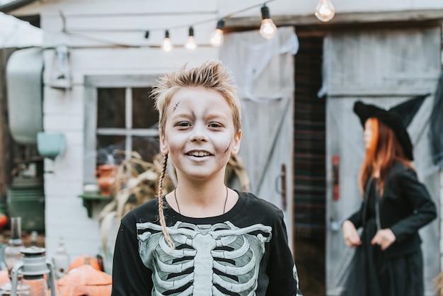 Un garçon dans un costume de squelette avec un visage peint sur le porche d'une maison décorée pour célébrer une fête d'halloween