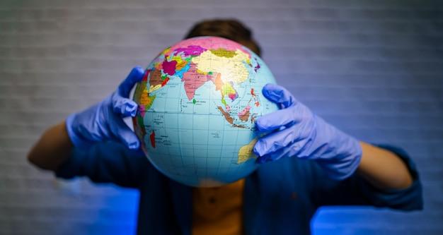 Le garçon dans des gants médicaux protecteurs montre le globe devant la caméra