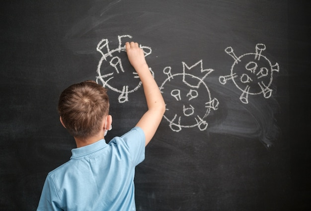 Un garçon dans un masque médical dessine un coronavirus sur un tableau noir