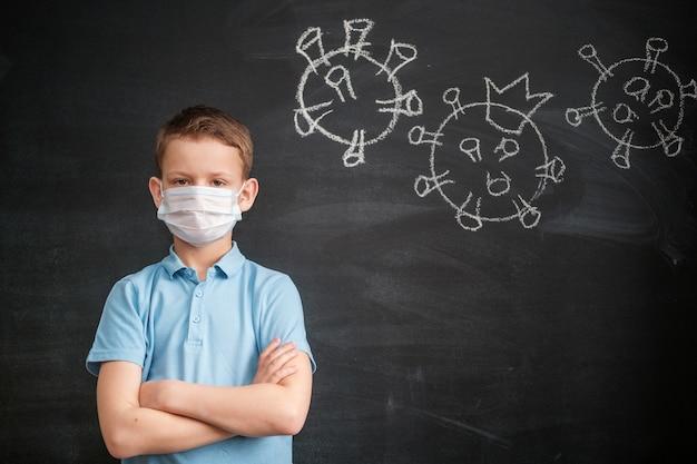 Garçon dans un masque médical sur le fond d'un tableau noir