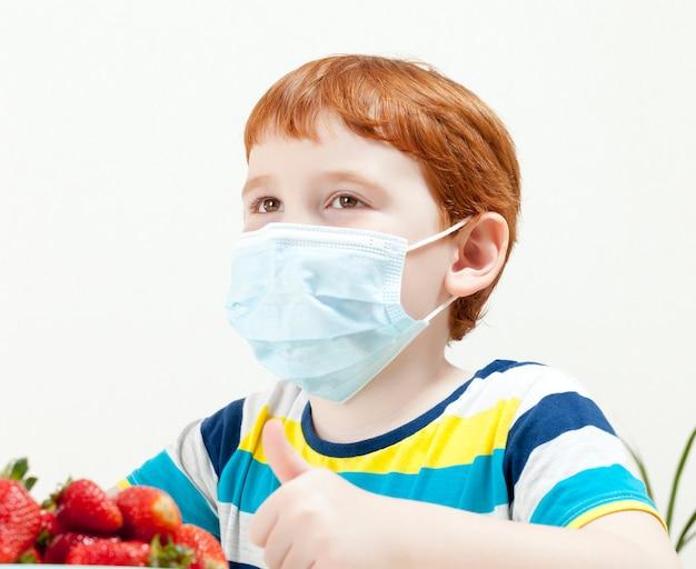 Un garçon dans un masque médical et des fraises mûres, le masque vous empêche de manger un dessert lors d'une pandémie de virus et de maladies