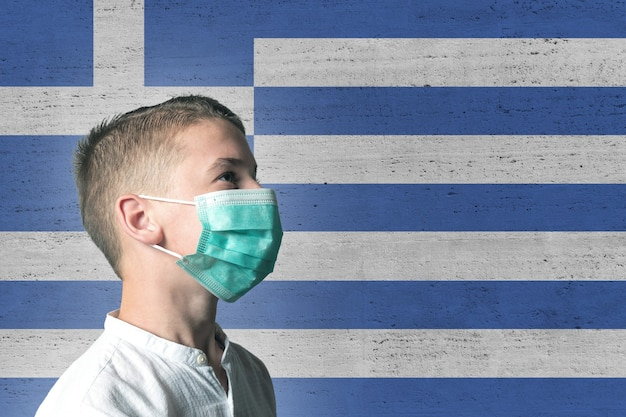 Garçon dans un masque médical sur son visage sur fond de drapeau de la grèce.