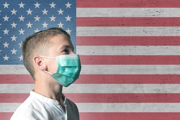 Garçon dans un masque médical sur son visage sur fond de drapeau usa.