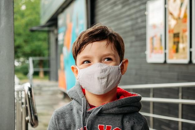 Un garçon dans un masque de protection entre dans le supermarché