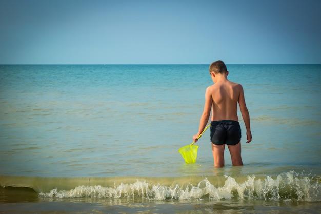 Garçon dans la mer. l'enfant part en mer avec un filet à papillons. concept de vacances pendant les vacances d'été