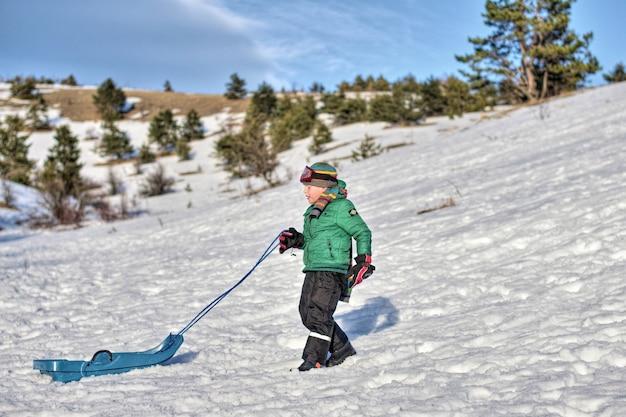Garçon dans les montagnes monte dans la neige sur un traîneau
