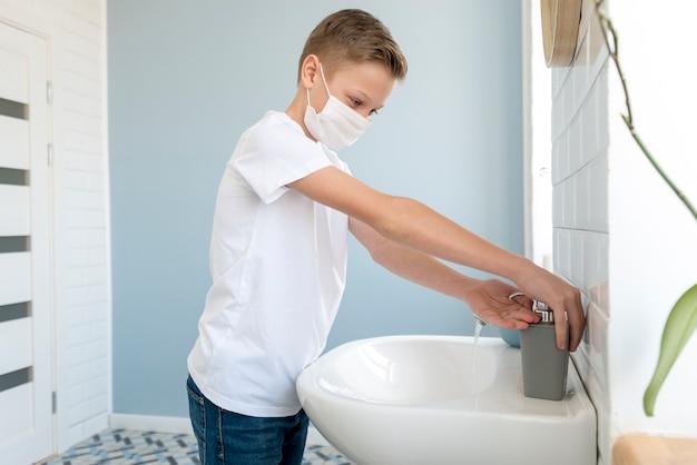 Garçon dans la salle de bain portant un masque médical