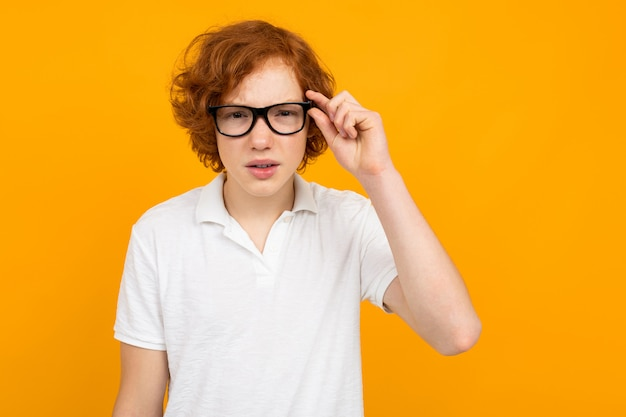 Garçon dans un t-shirt blanc loucher dans des verres sur fond jaune