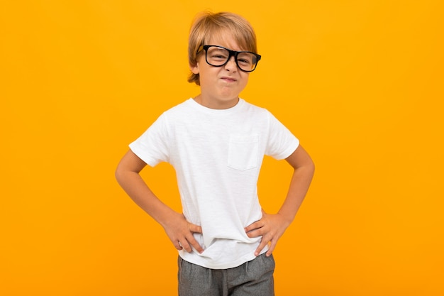 Garçon dans un t-shirt blanc loucher dans des verres sur jaune avec copie espace