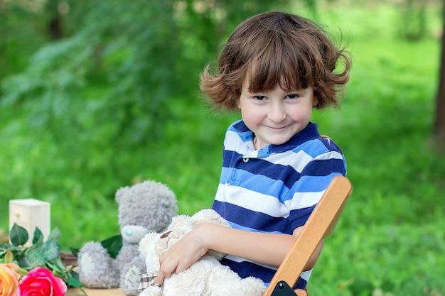 Le garçon dans un t-shirt bleu rayé est assis sur un tabouret à l'extérieur parmi les verts