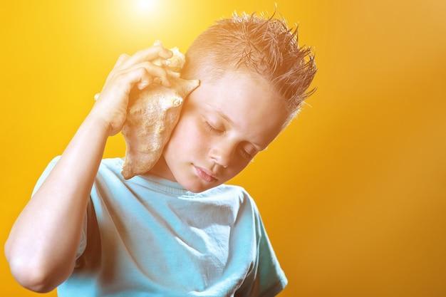 Un garçon dans un t-shirt léger écoute la mer dans un coquillage sur un fond coloré