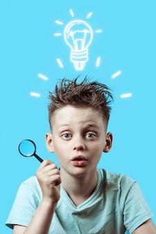 Un garçon dans un t-shirt léger tenant une petite loupe sur bleu